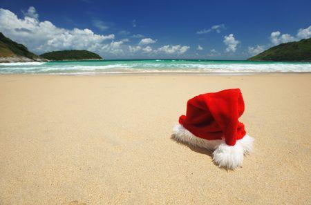 tropical christmas: Santas hat on a tropical beach