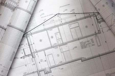 House plan blueprints roled up over table photo
