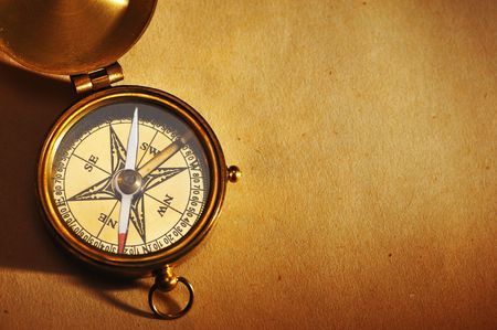 compass map: Antique brass compass over old paper background