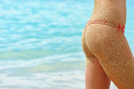 Woman on a beach in bikini with a sandy back photo