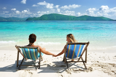 Couple on a tropical beach in chaise lounge photo