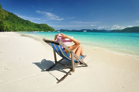 Girl on a tropical beach in chaise lounge Stock Photo - 6411248