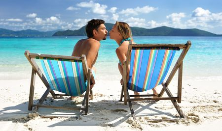 chaise lounge: Couple kissing on a tropical beach in chaise lounge