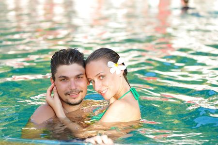 Couple in tropical swimming pool photo