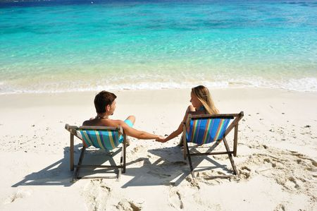 chaise lounge: Couple on a tropical beach in chaise lounge