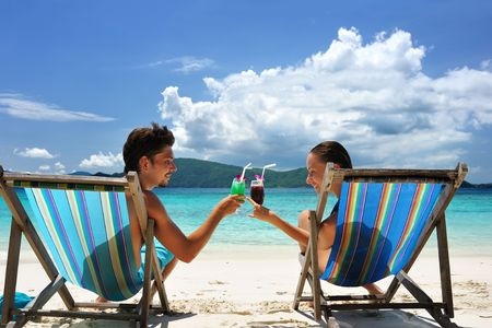 Couple on a tropical beach in chaise lounge Stock Photo - 6607653