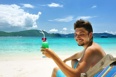 caribbean drink: Man on a beach with cocktail