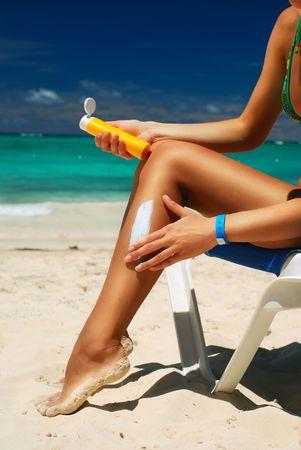 Tan woman applying sun protection lotion photo