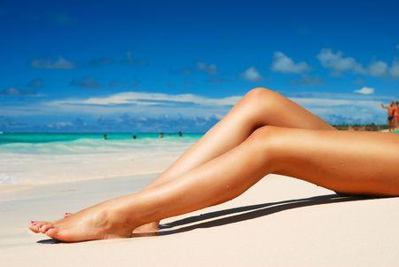 Womens sexy legs on the beach Stock Photo