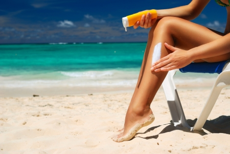 Tan woman applying sun protection lotion Stock Photo - 6681202