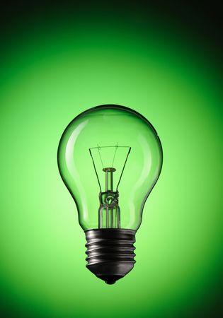 green light bulb: Light Bulb over green background Stock Photo