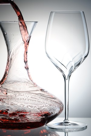 Pouring red wine into decanter photo