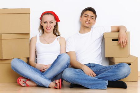 family moving house: Young couple resting from moving into a new home