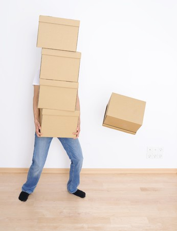 packing boxes: Young man carrying and dropping his stack of moving boxes