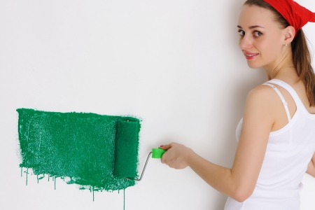 Woman painting interior wall of home with paint roller Stock Photo - 7089948