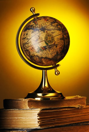 Antique globe on old books over yellow photo