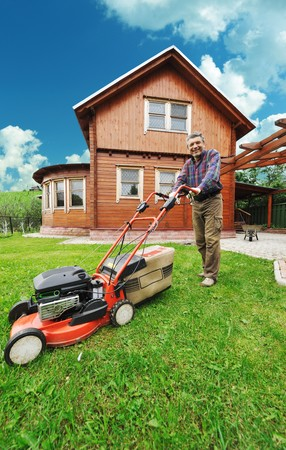 frontyard: Senior man mowing the lawn Stock Photo