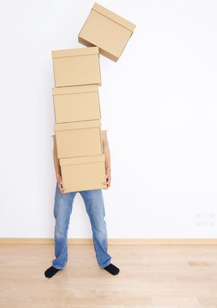 family moving house: Young man carrying and dropping his stack of moving boxes