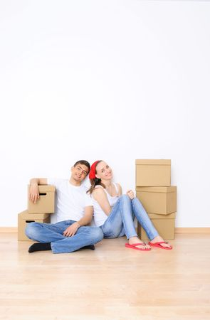 family moving house: Young couple resting from moving into a new home. Great copy space.