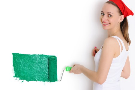 painting and decorating: Woman painting interior wall of home with paint roller