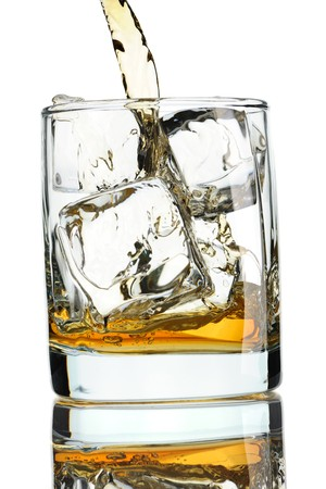 Pouring whiskey in glass with ice isolated on white photo