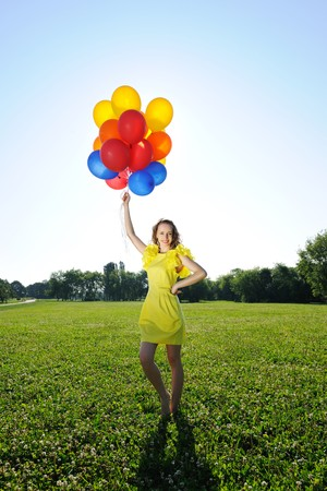 against the sun: Woman holding balloons against sun and sky