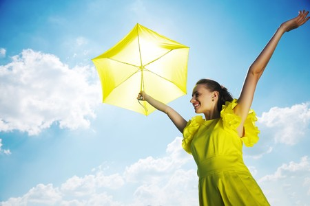 against the sun: Woman holding umbrella against sun and sky