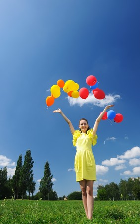 release: Woman releasing balloons against sky Stock Photo