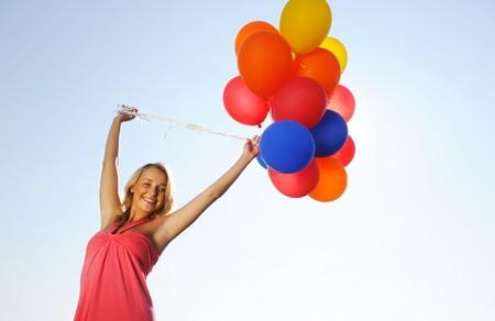 Mujer sosteniendo globos contra el sol y el cielo  Foto de archivo - 7619300