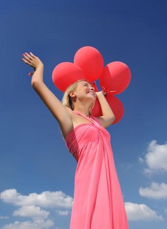 Mujer sosteniendo globos contra el sol y el cielo  Foto de archivo - 7694260