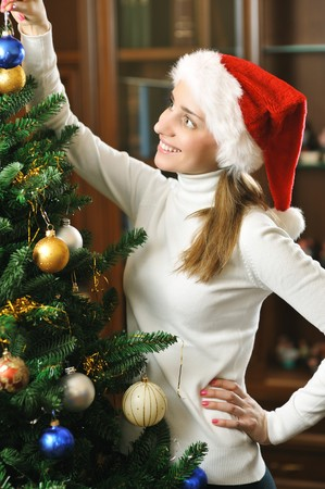 Young woman decorating christmas tree photo
