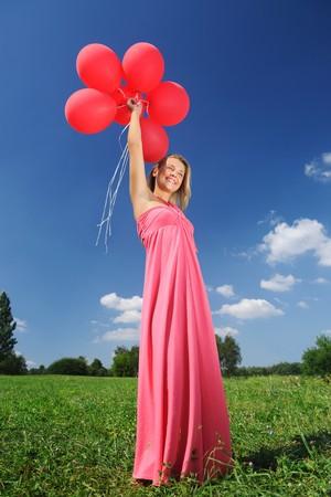 Mujer sosteniendo globos contra el sol y el cielo  Foto de archivo - 7824761