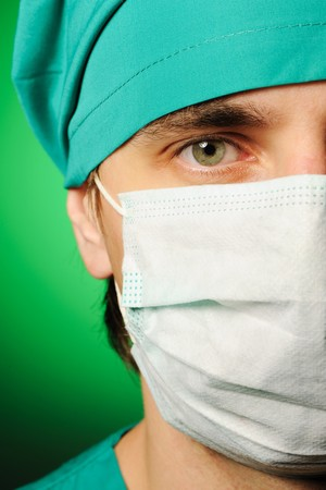 Surgeon in mask over green Stock Photo - 7837880