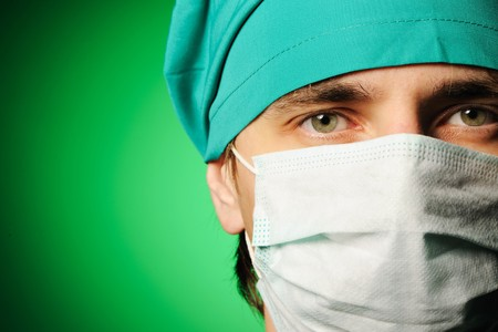 Surgeon in mask over green
