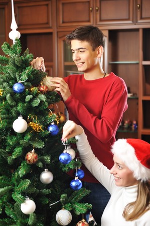 Young couple decorating christmas tree photo
