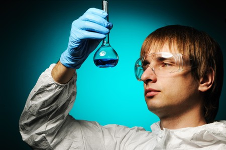 Scientist in protective wear and glasses looking at chemical flask photo