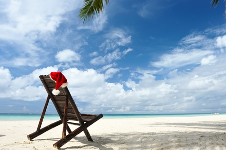 Santas hat and chaise lounge on the beach photo