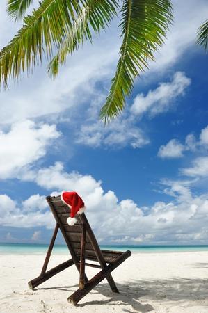 ビーチでサンタさんの帽子とシェーズ ラウンジ 写真素材