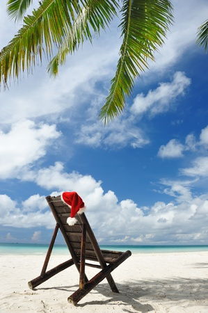 Santa's hat and chaise lounge on the beach Standard-Bild