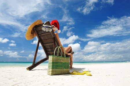 Woman relaxing on the beach in santas hat photo