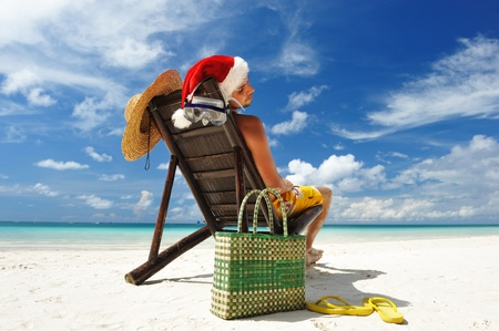 Man relaxing on the beach in santas hat Stock Photo