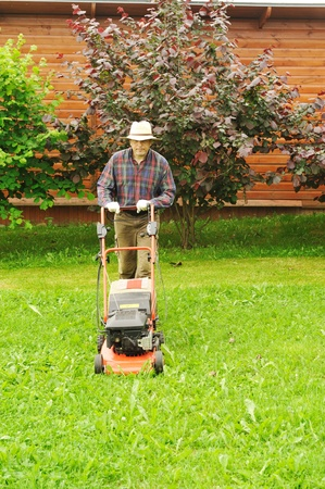 Senior man mowing the lawn photo