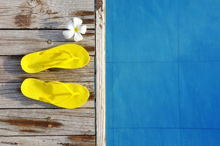 summer holiday: Yellow sandals by a swimming pool  Stock Photo