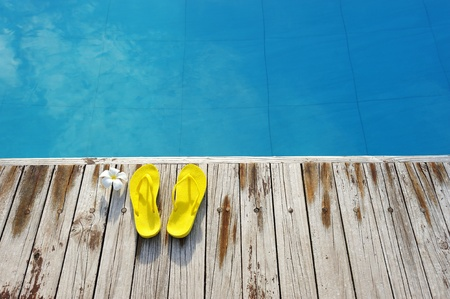 swimming shoes: Yellow sandals by a swimming pool  Stock Photo