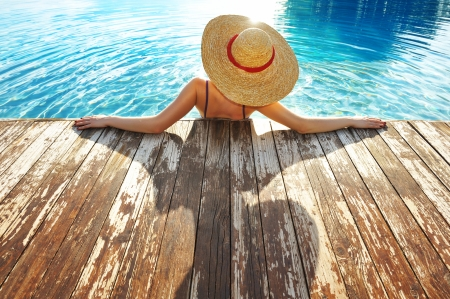 hat nude: Woman in hat relaxing at the pool