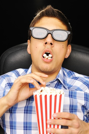 watching movie: Young man watching movie in 3D glasses at cinema
