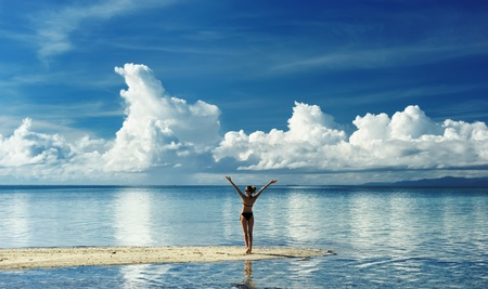 Girl on a tropical beach with outstretched arms Фото со стока