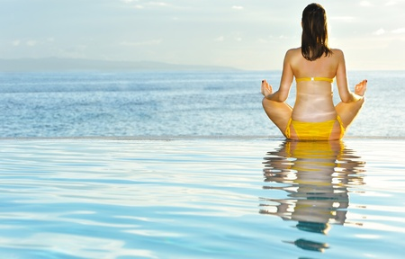 Woman doing yoga exercise at poolside Stock Photo