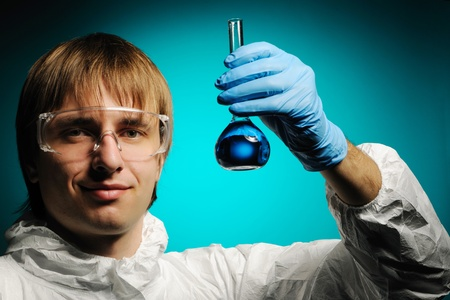 Scientist in protective wear and glasses showing flask with reagent photo