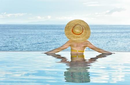 Vrouw in hoed ontspannen aan het zwembad